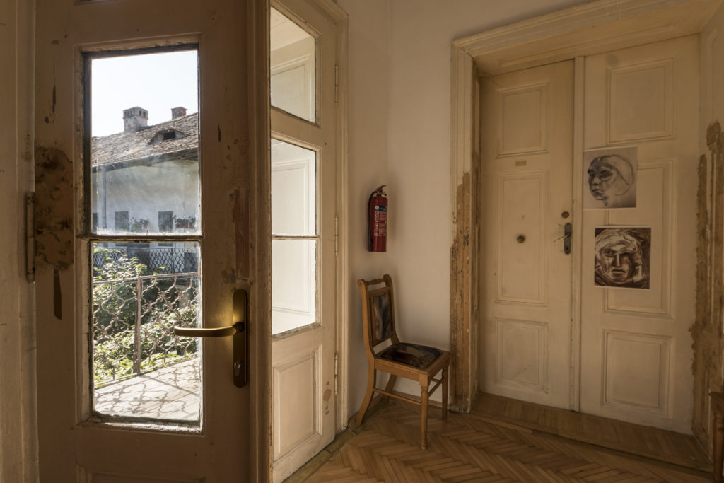 Picture of a room in an older building with two doors. One of them is leading to a terrace while the other one is closed.